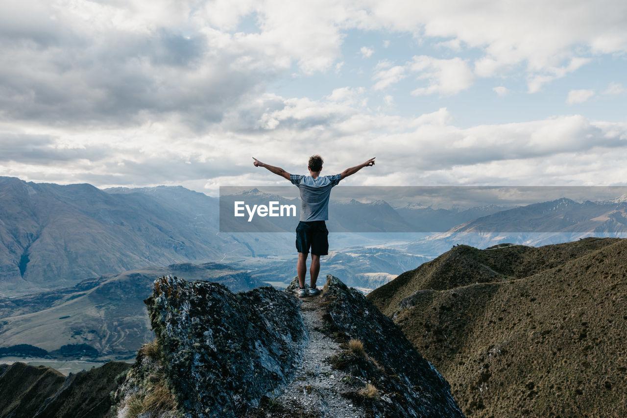 Full Length Of Men Standing On Mountain Against Sky