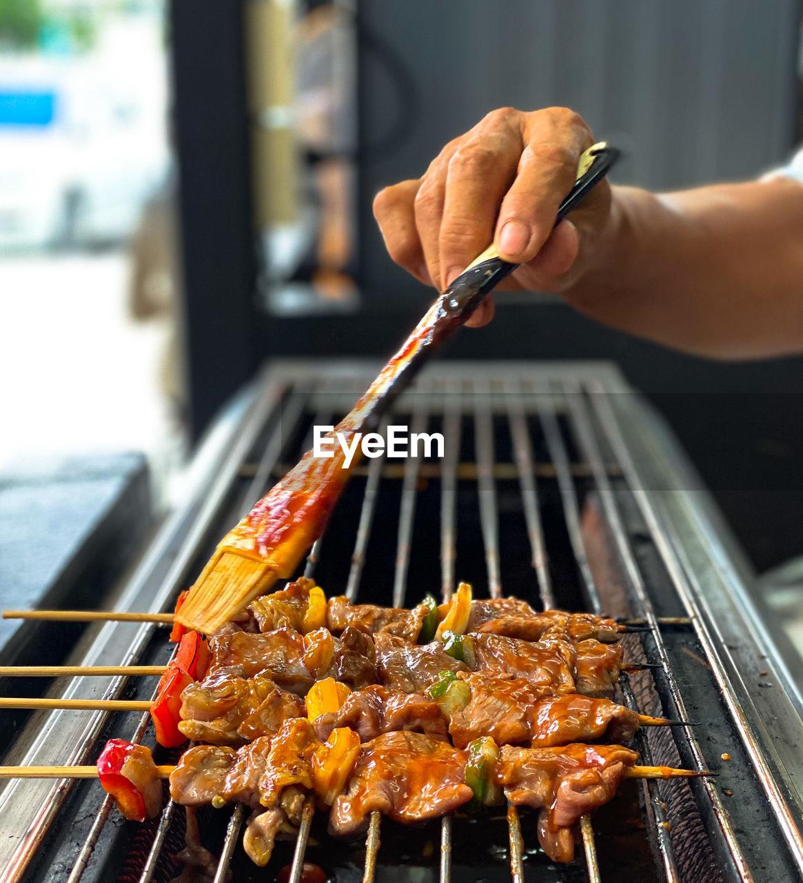 CROPPED IMAGE OF PERSON PREPARING FOOD ON BARBECUE
