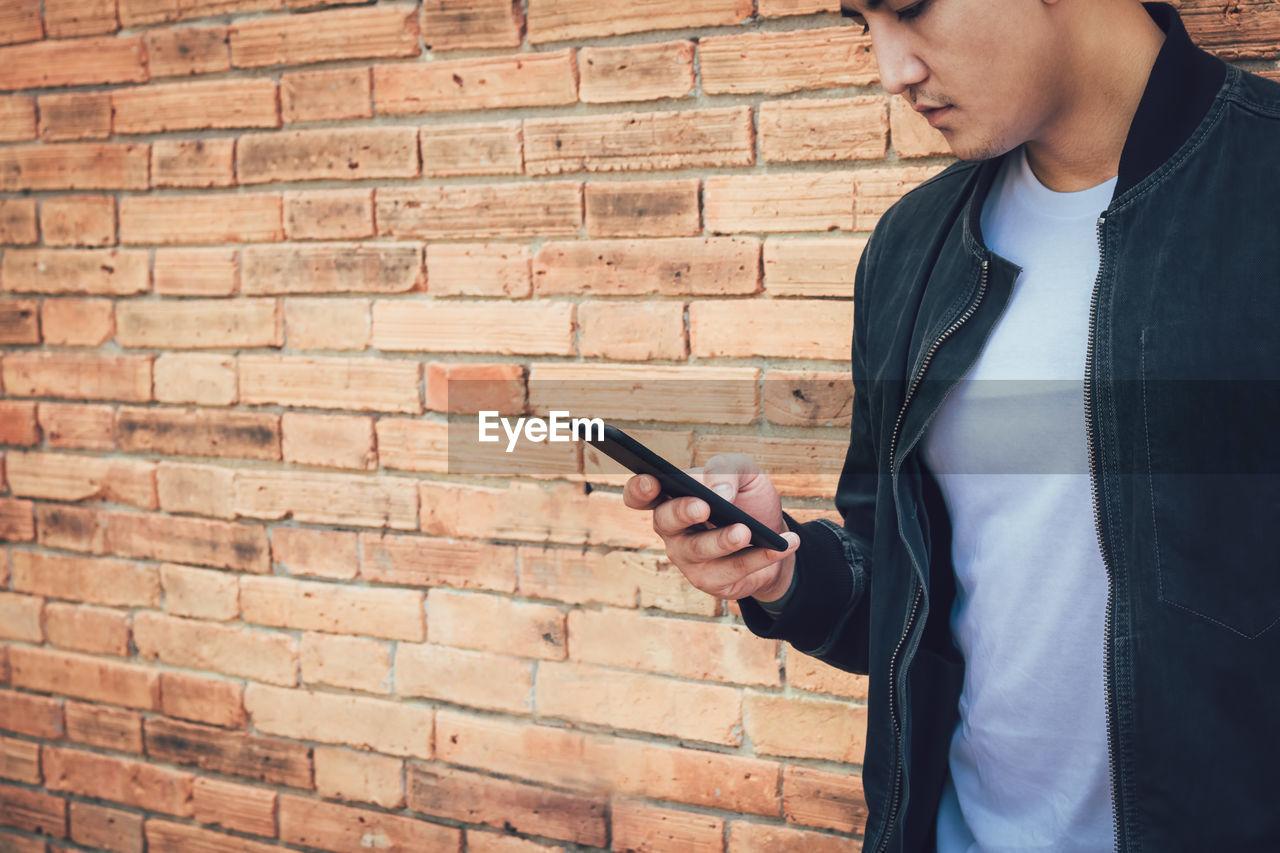 Man using mobile phone against brick wall