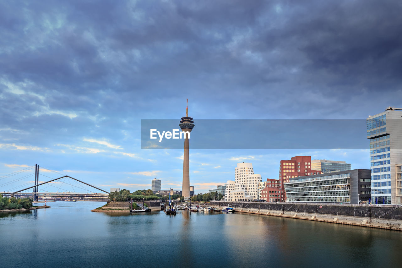 architecture, built structure, building exterior, sky, tower, travel destinations, cloud - sky, city, water, day, outdoors, tourism, travel, no people, river, communication, transportation, television tower, skyscraper, nature