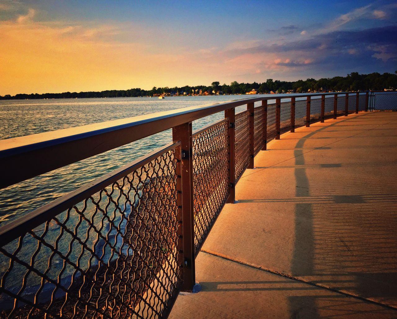 Empty walkway along calm sea