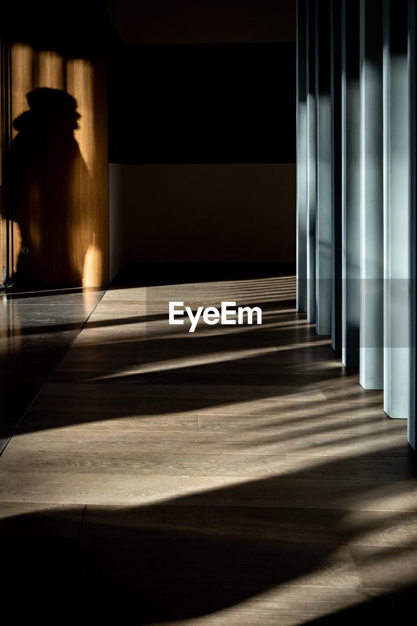shadow, sunlight, indoors, flooring, architecture, no people, arcade, absence, corridor, empty, nature, hardwood floor, building, built structure, illuminated, wood - material, dark, day, luxury