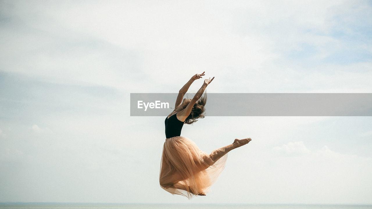 Woman dancing over sea against sky