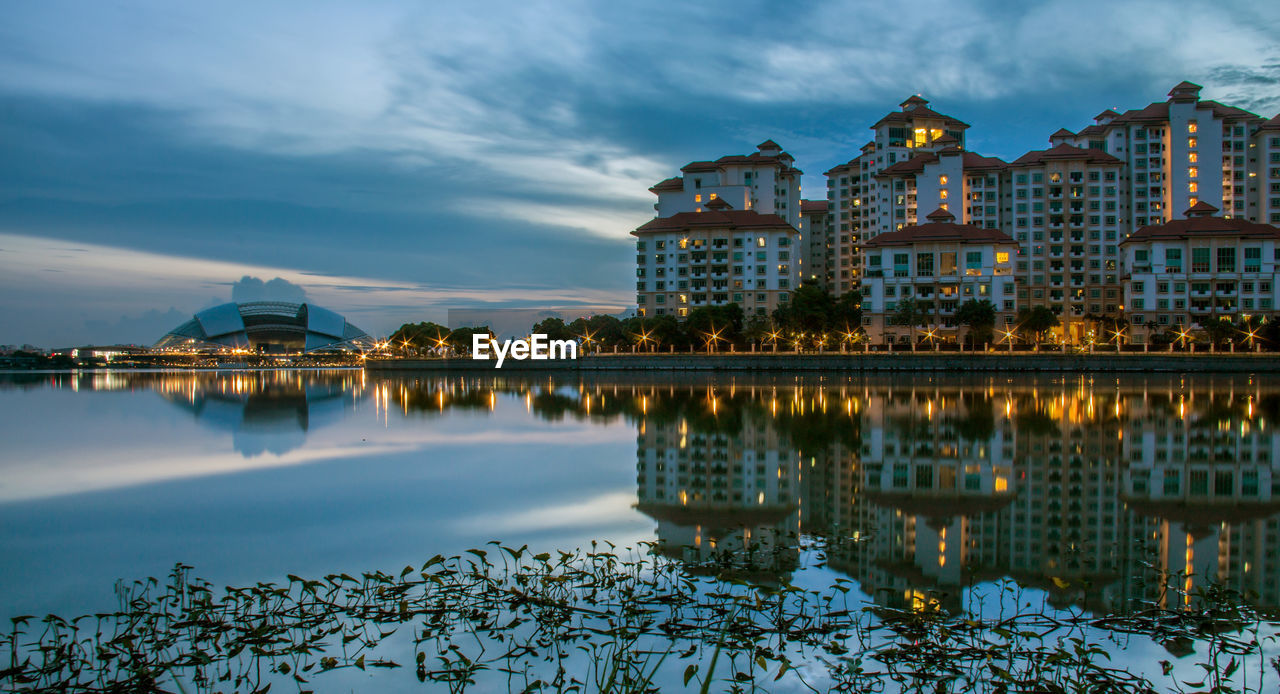 Illuminated buildings by river in kallang against sky