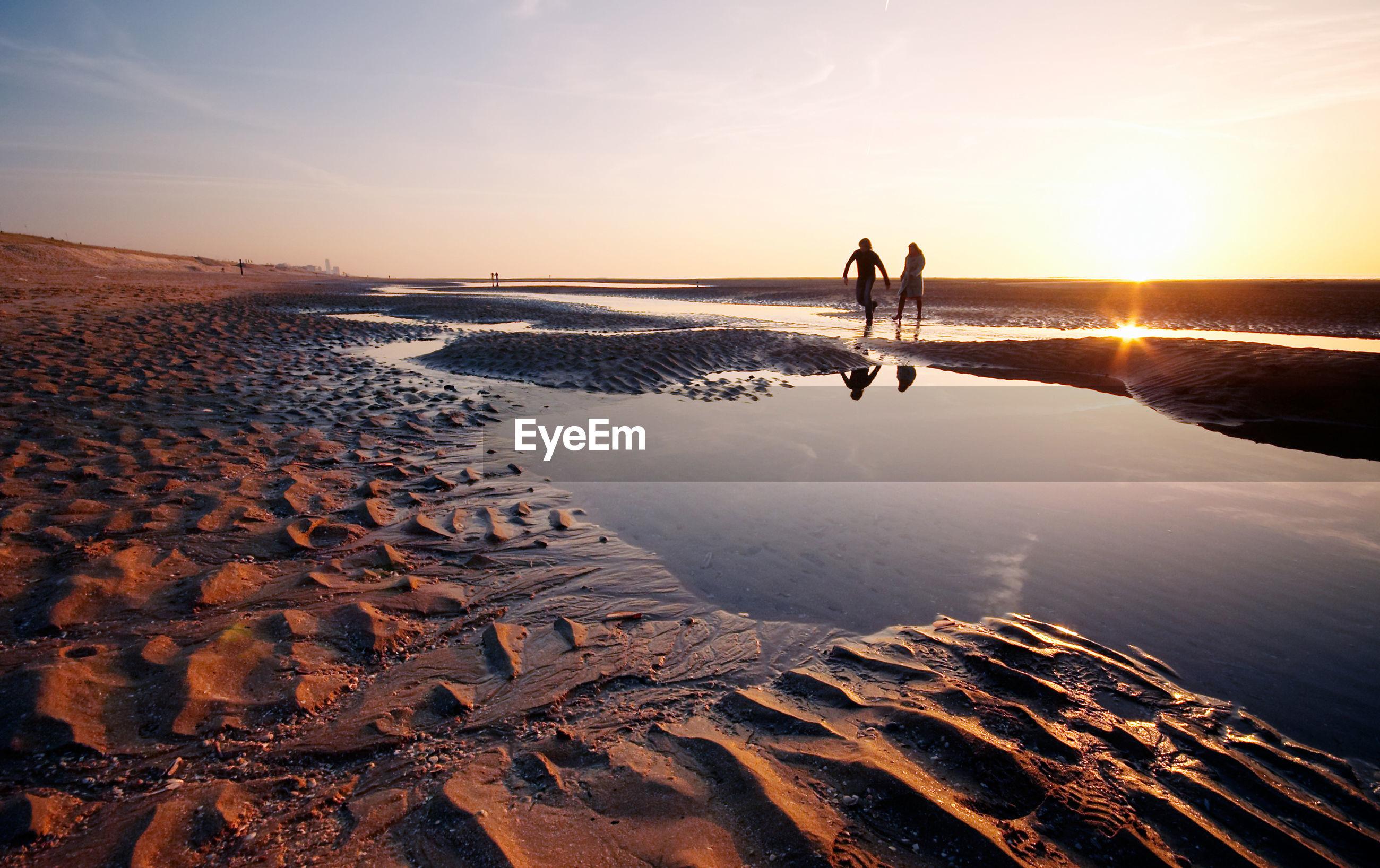 Silhouette couple walking on beach