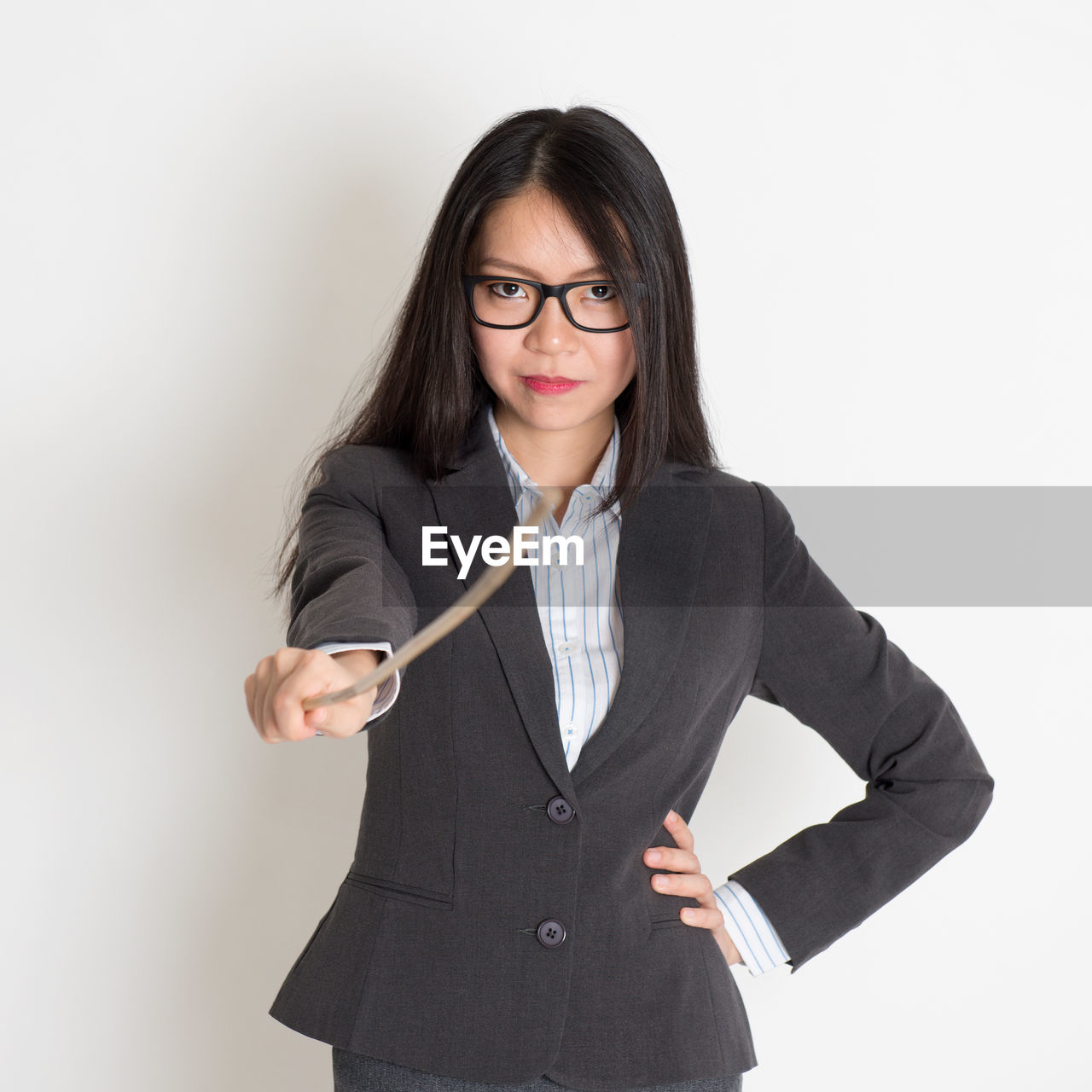 Portrait of businesswoman holding stick against white background