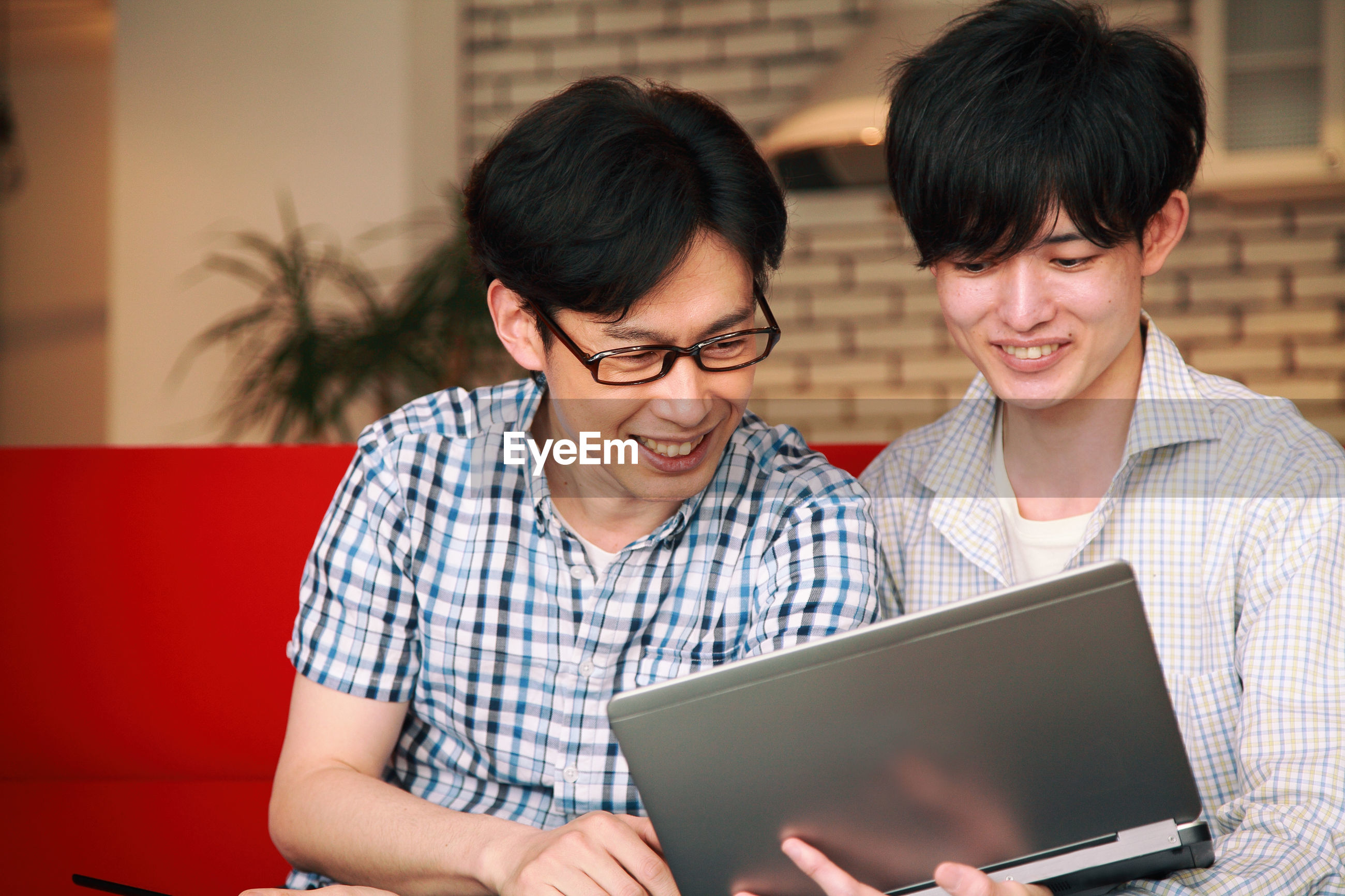 Close-up of friends using digital tablet while sitting on sofa at home