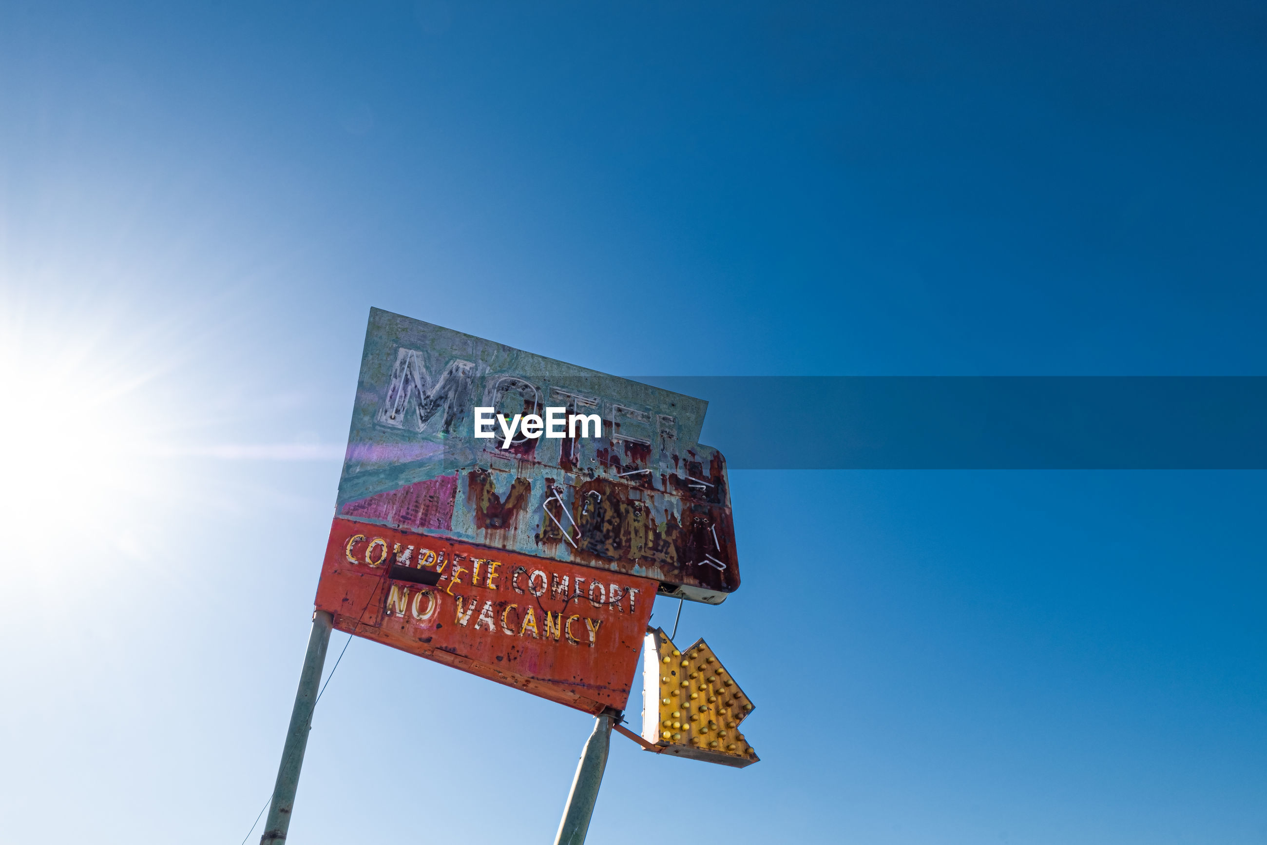 LOW ANGLE VIEW OF SIGN BOARD AGAINST SKY
