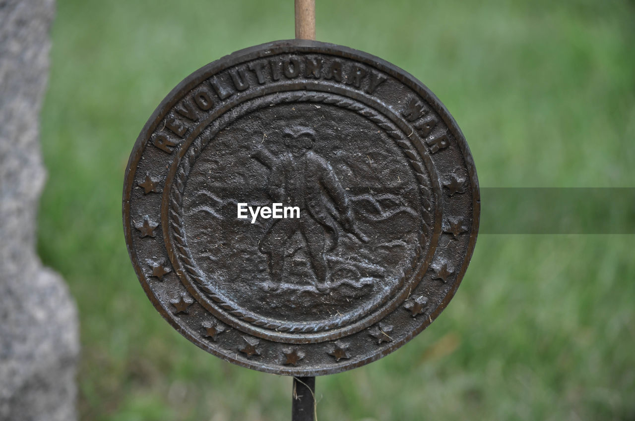 circle, metal, text, close-up, coin, no people, day, focus on foreground, communication, outdoors