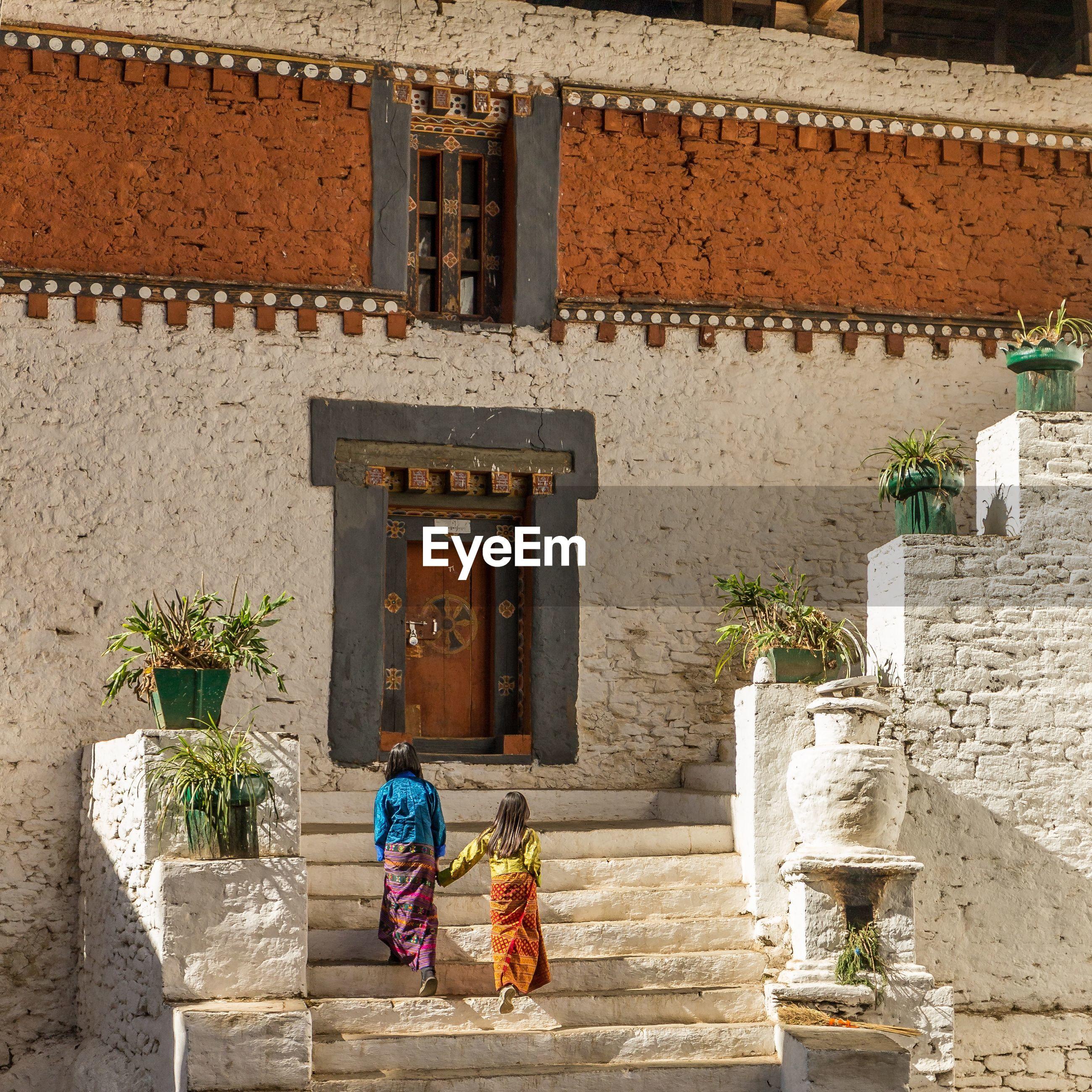 Sisters walking on steps against house