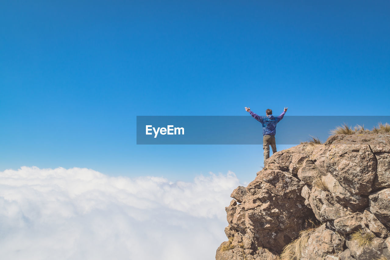 Low Angle View Of Man Standing On Mountain Peak