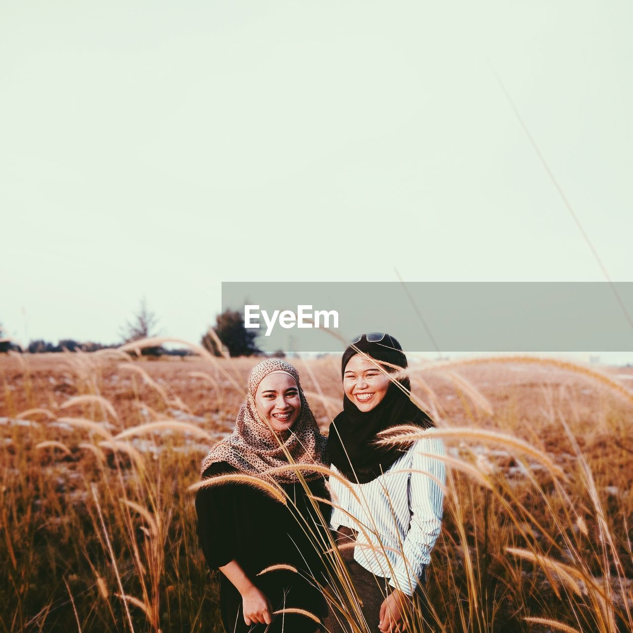Smiling Female Friends Standing Amidst Plants On Field