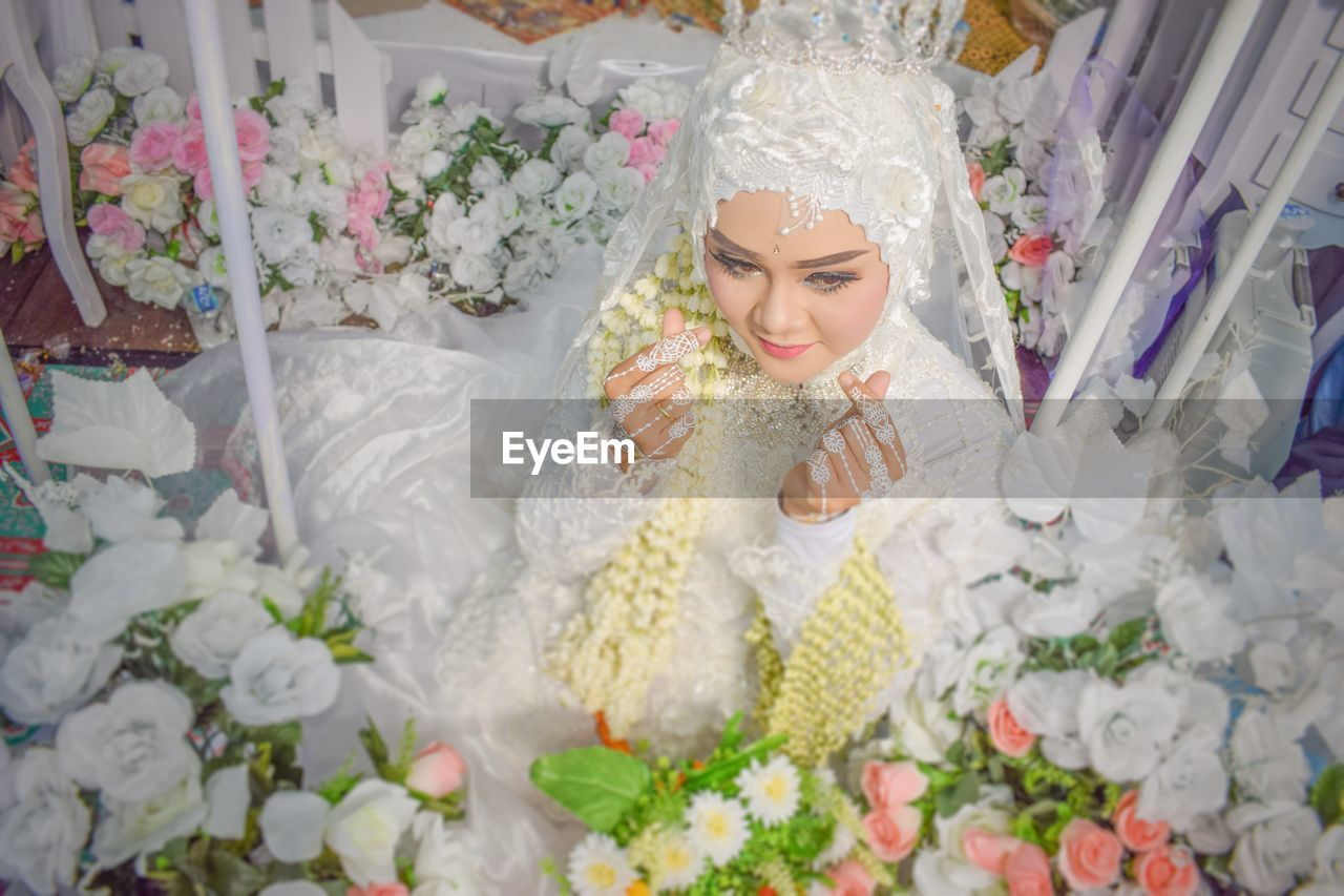 Bride looking away while sitting amidst flowers
