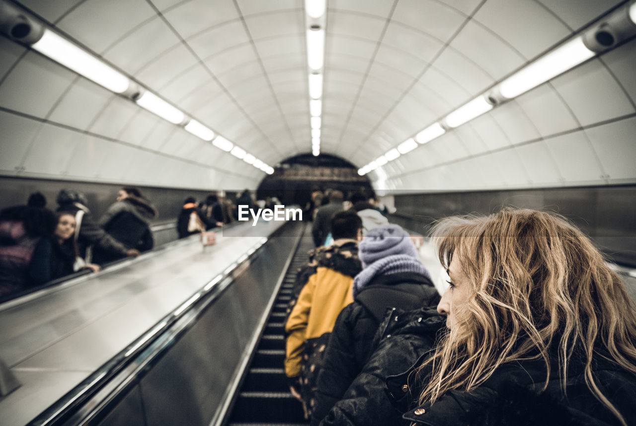 real people, transportation, large group of people, rear view, public transportation, indoors, women, lifestyles, men, train - vehicle, subway station, passenger, journey, rail transportation, technology, leisure activity, sitting, modern, day, adult, people