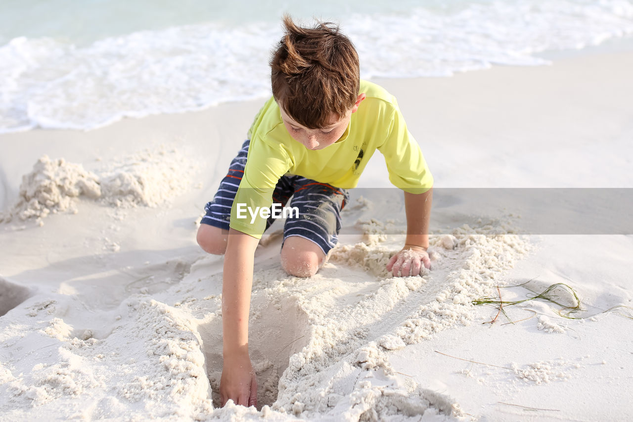 Boy Making Sandcastle At Beach