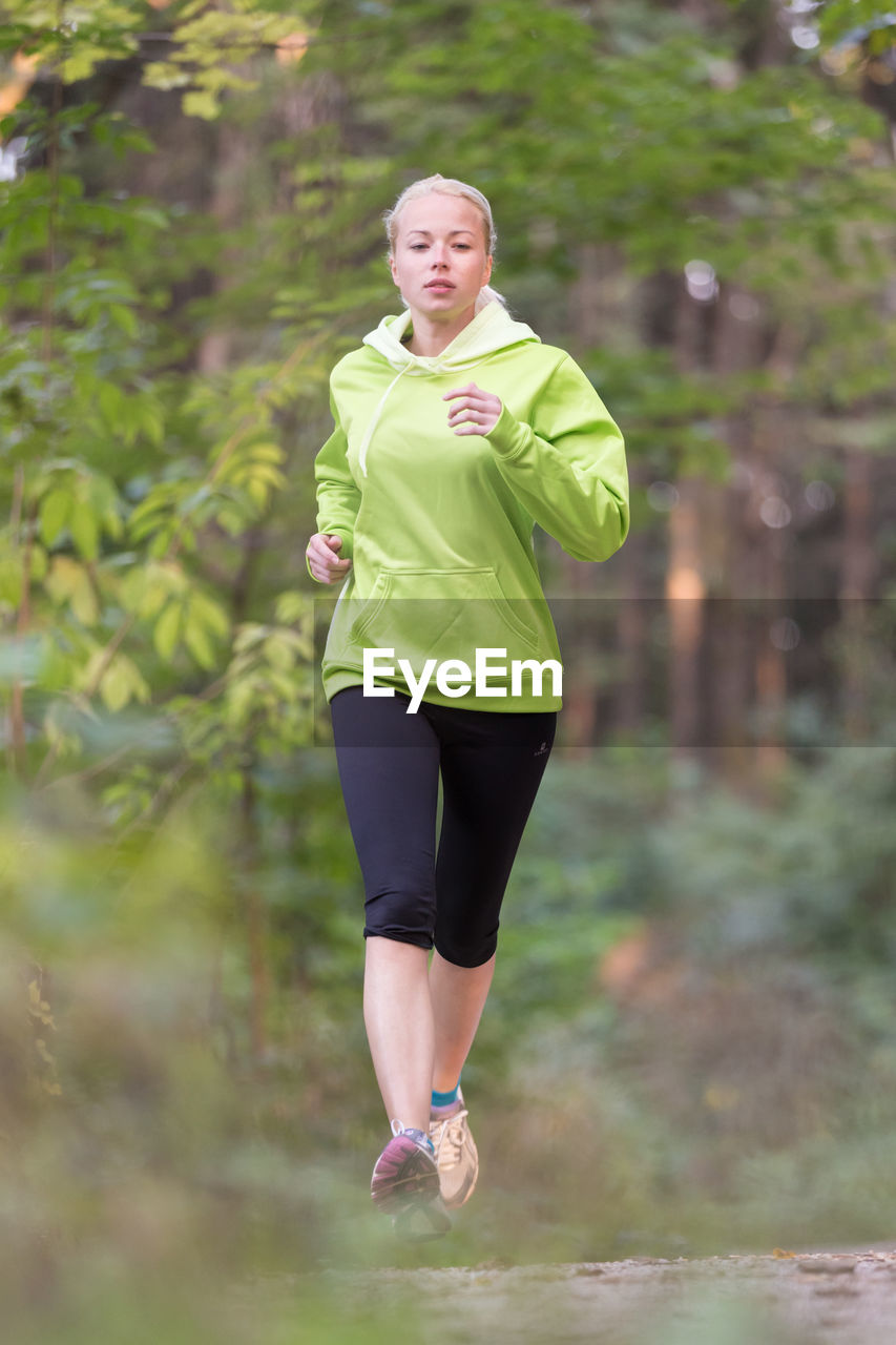 Full length of a woman running on plant