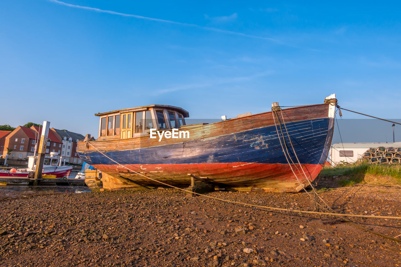 sky, transportation, nautical vessel, mode of transportation, day, nature, moored, no people, beach, blue, land, abandoned, water, outdoors, old, travel, tranquility, sand, ship, architecture, sailboat, anchored