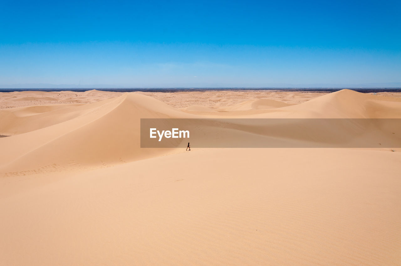 Teenage girl on desert against sky