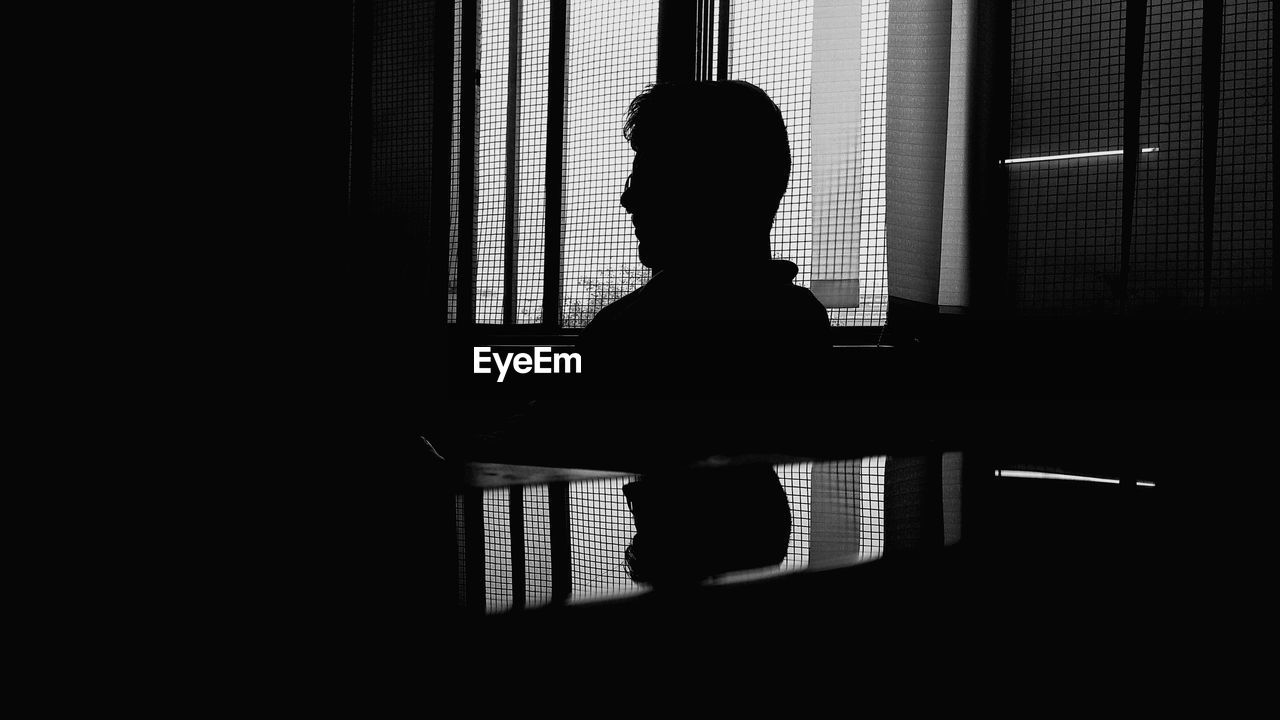 SIDE VIEW OF SILHOUETTE MAN SITTING AGAINST WINDOW AT HOME
