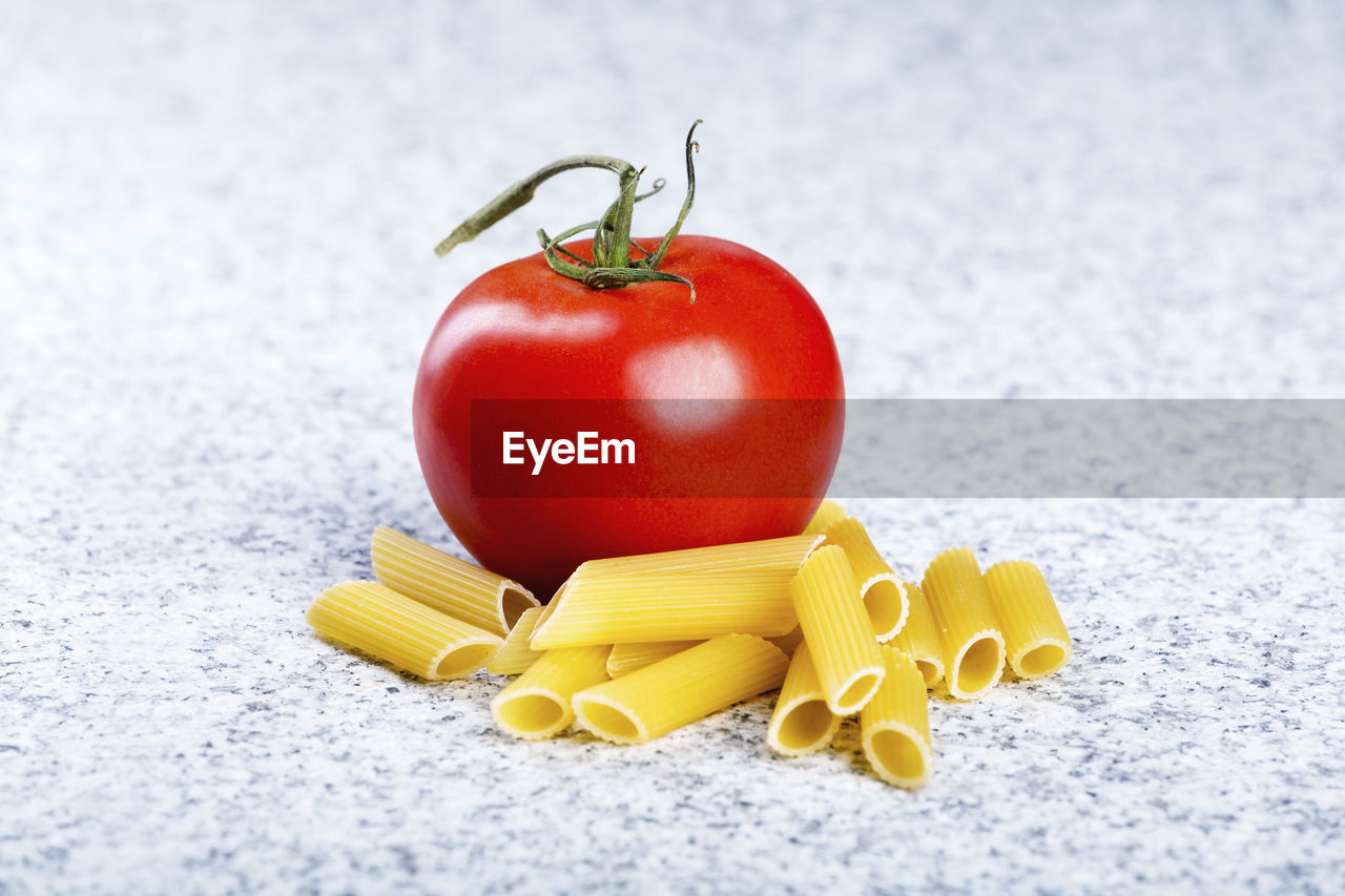 Close-up of raw pasta with tomato on table