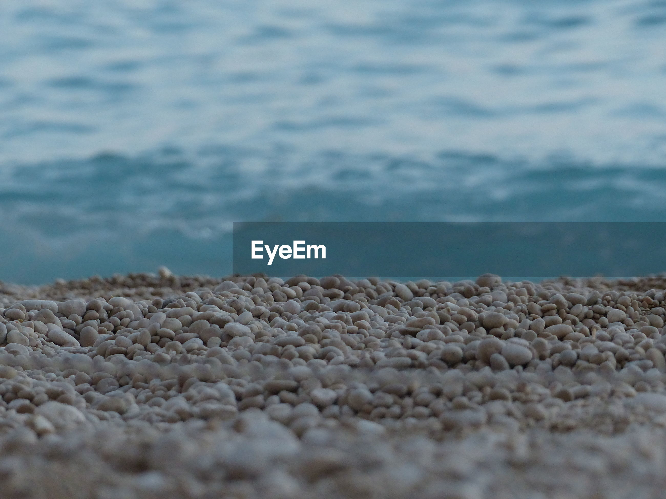 Close-up of pebbles against sea