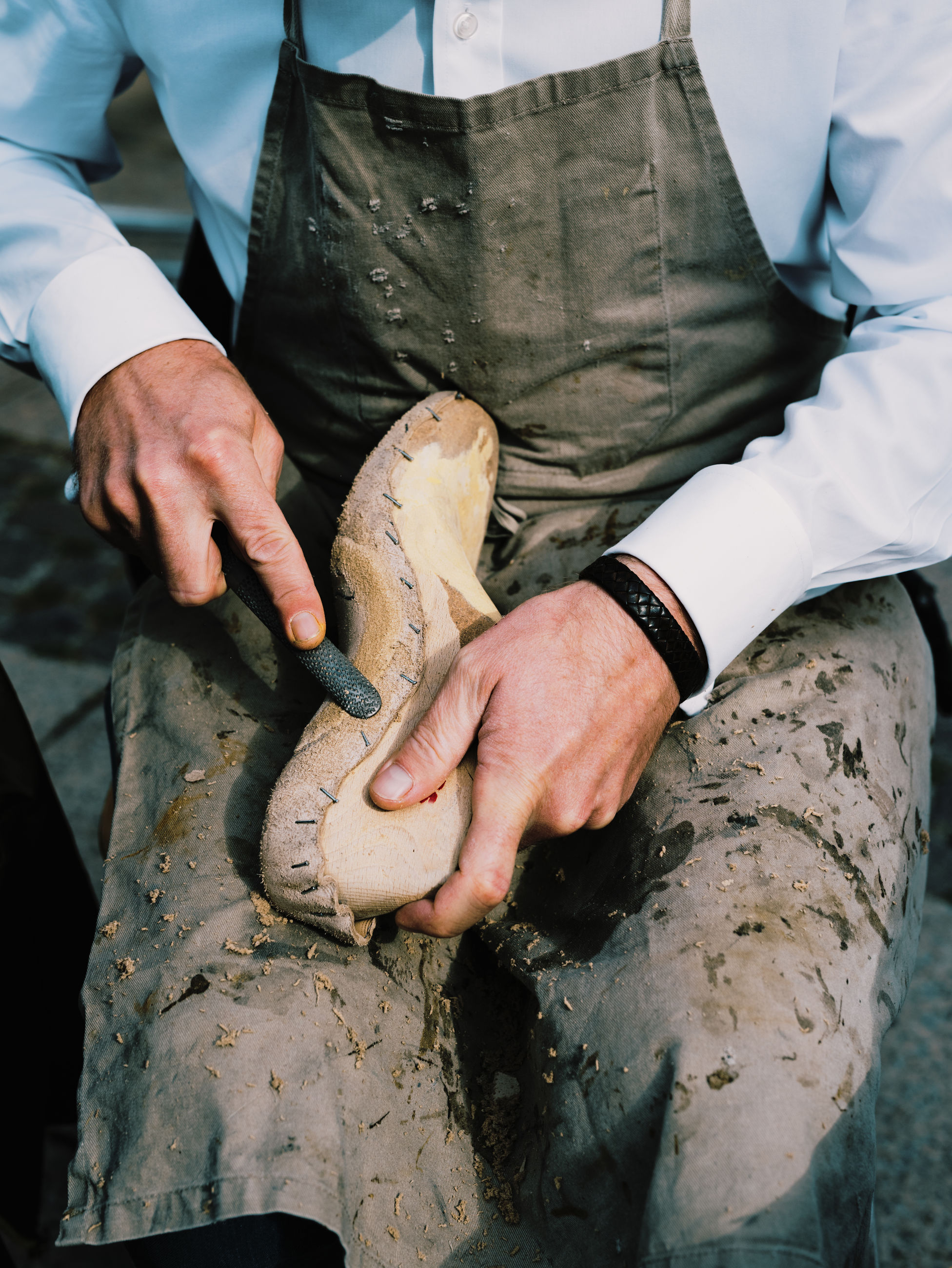 Close-up of man carving shoes at workshop
