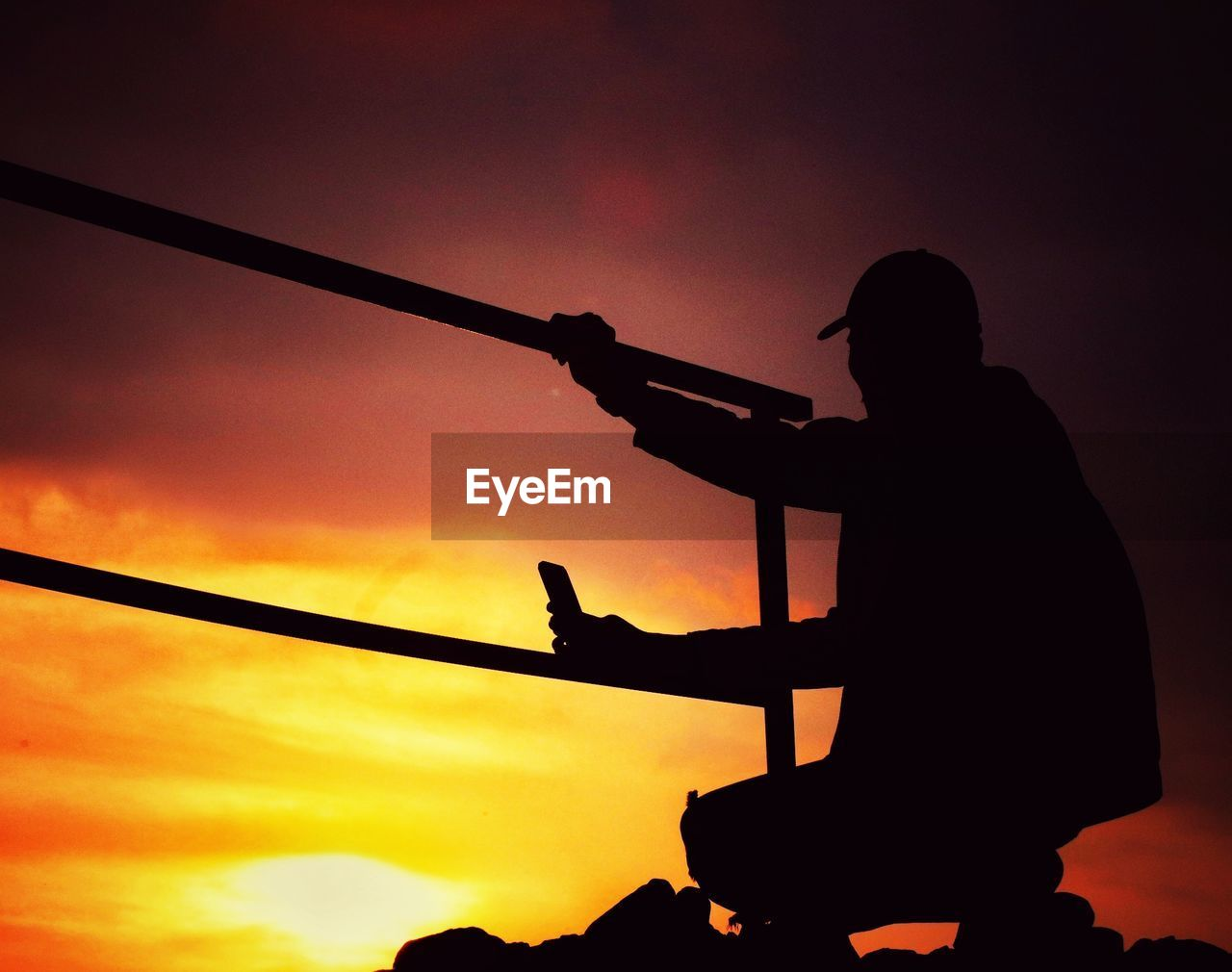 silhouette, sunset, sky, real people, orange color, one person, lifestyles, men, holding, leisure activity, nature, sport, standing, playing, skill, beauty in nature, cloud - sky, outdoors, weapon