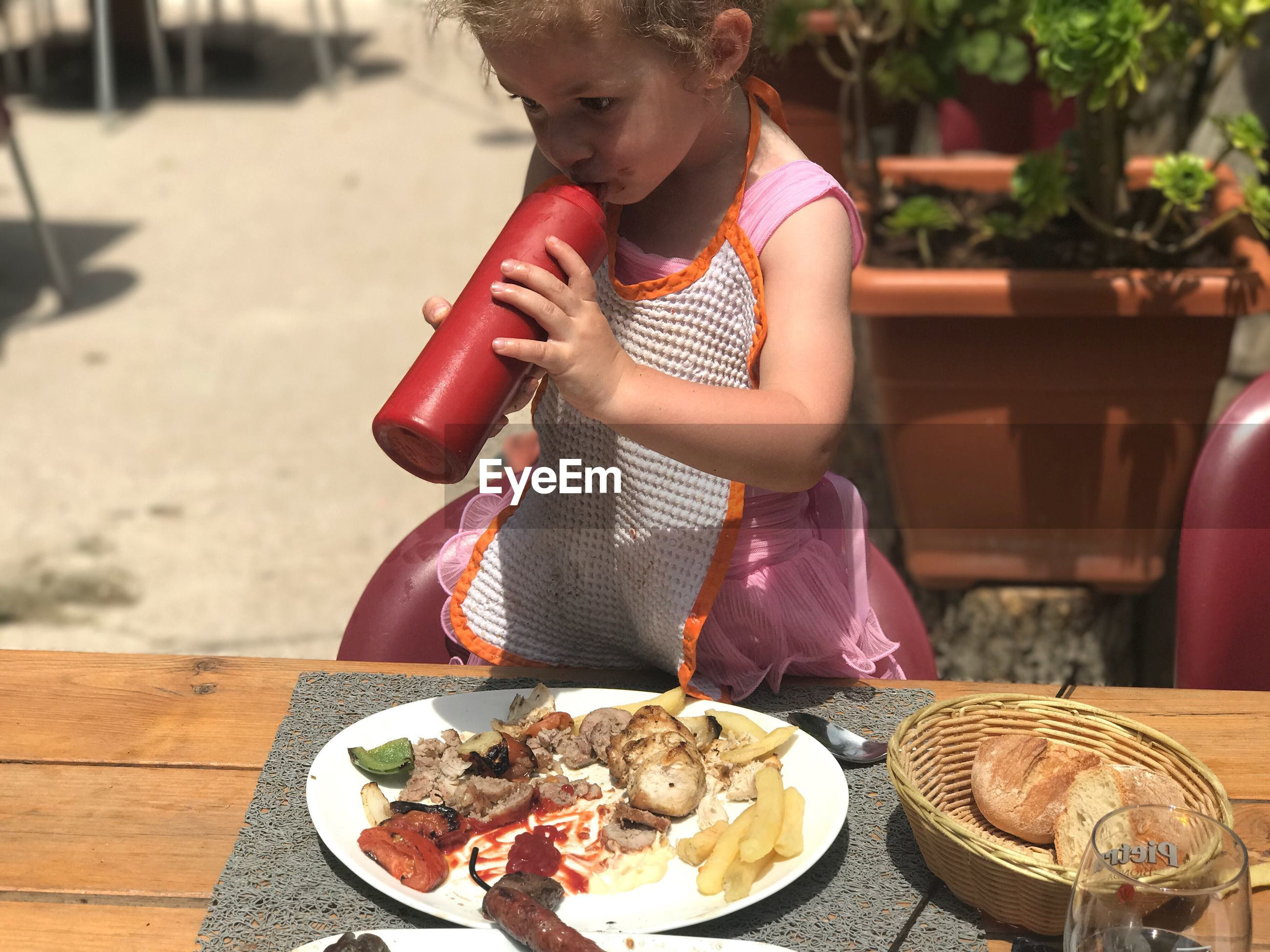 Little girl drinking ketchup from bottle at table