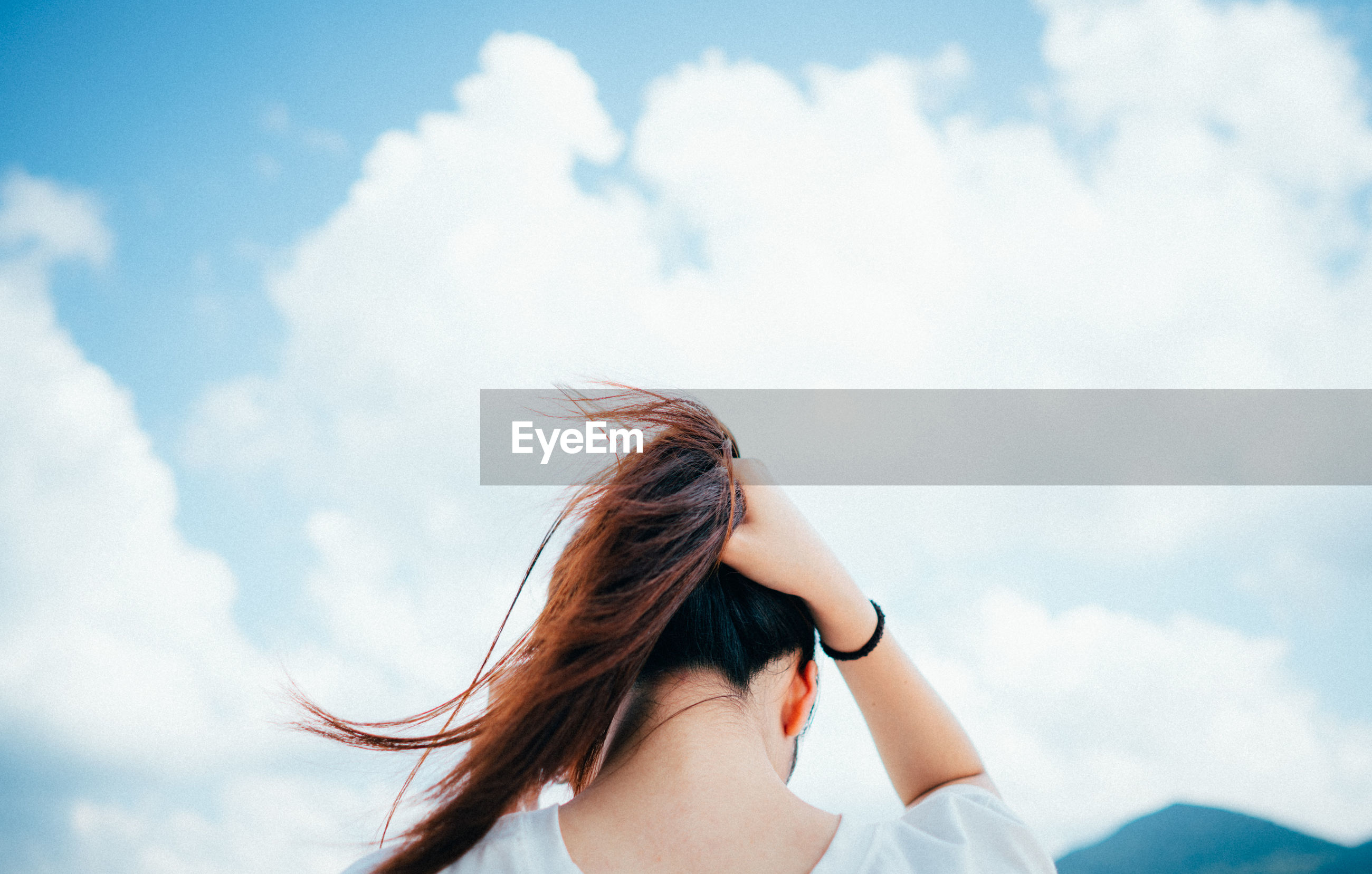 Young woman looking away against sky
