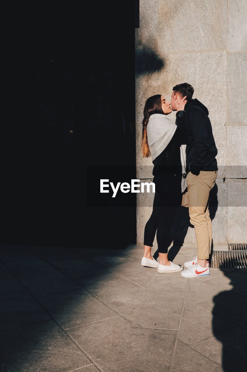 two people, love, togetherness, real people, full length, standing, lifestyles, leisure activity, casual clothing, young men, men, indoors, couple - relationship, young women, young adult, bonding, day, architecture, adult, people