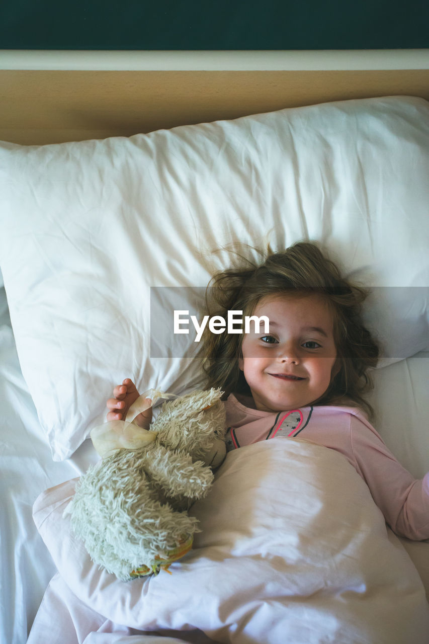 childhood, child, looking at camera, furniture, portrait, bed, indoors, smiling, real people, one person, cute, girls, happiness, high angle view, home interior, women, innocence