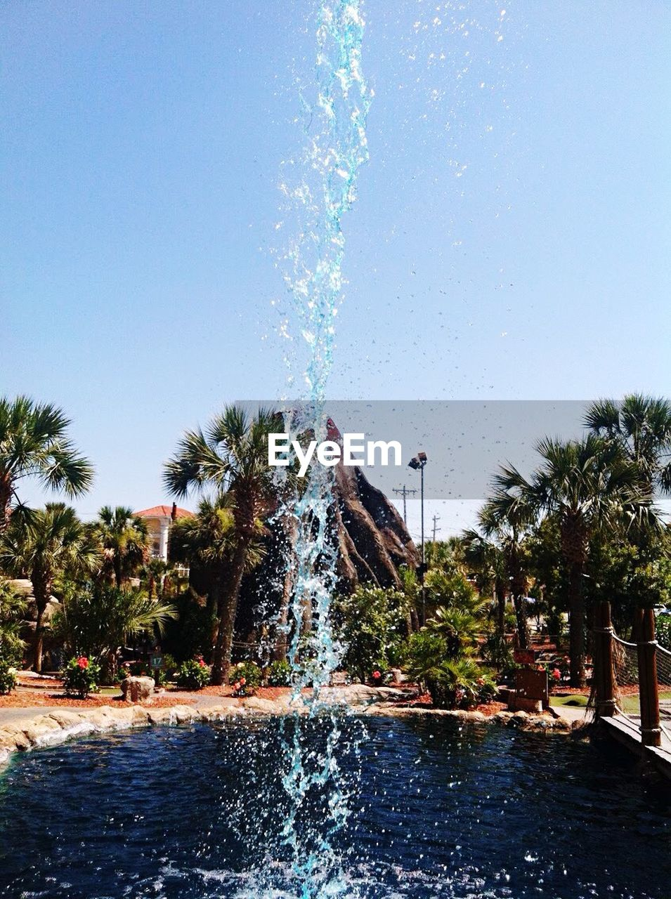 water, fountain, splashing, spraying, motion, tree, palm tree, nature, water park, swimming pool, clear sky, tourist resort, outdoors, long exposure, day, sky, vacations, beauty in nature, waterfall, blue, water slide, power in nature, architecture, building exterior, no people