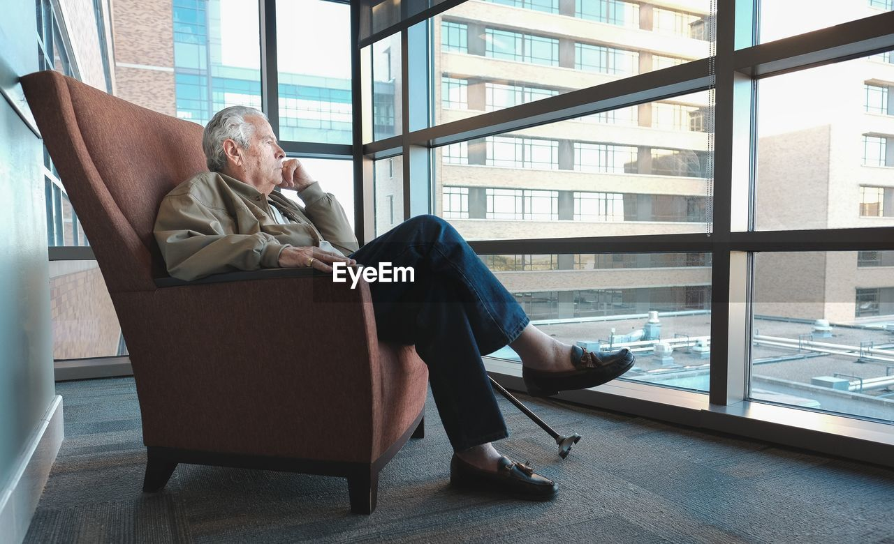 window, indoors, sitting, full length, adult, men, real people, males, chair, seat, people, day, senior adult, relaxation, senior men, casual clothing, lifestyles, leisure activity, transparent, armchair