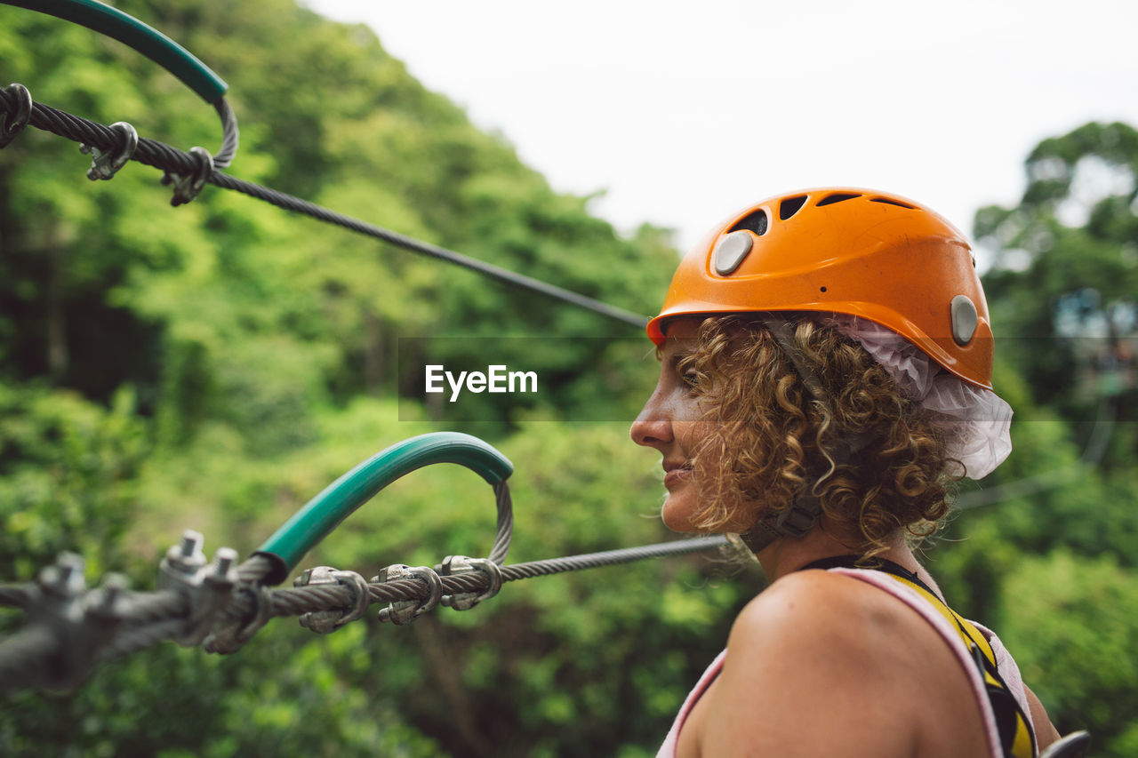 Woman Wearing Helmet By Safety Harness Against Trees