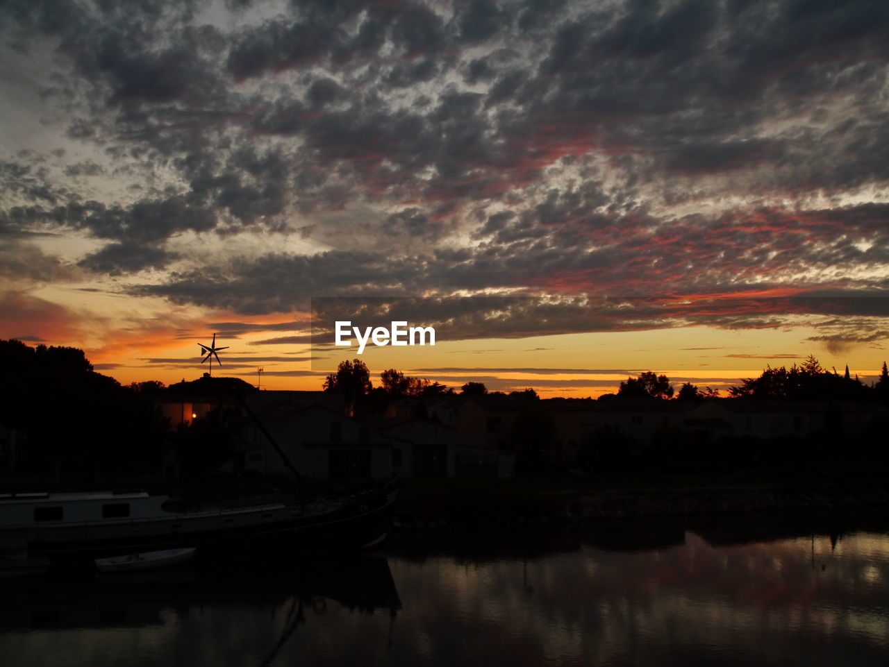 sunset, cloud - sky, sky, reflection, nautical vessel, dramatic sky, orange color, water, silhouette, no people, beauty in nature, nature, built structure, scenics, building exterior, tranquility, transportation, travel destinations, mode of transport, tranquil scene, outdoors, architecture, tree, moored, yacht, city