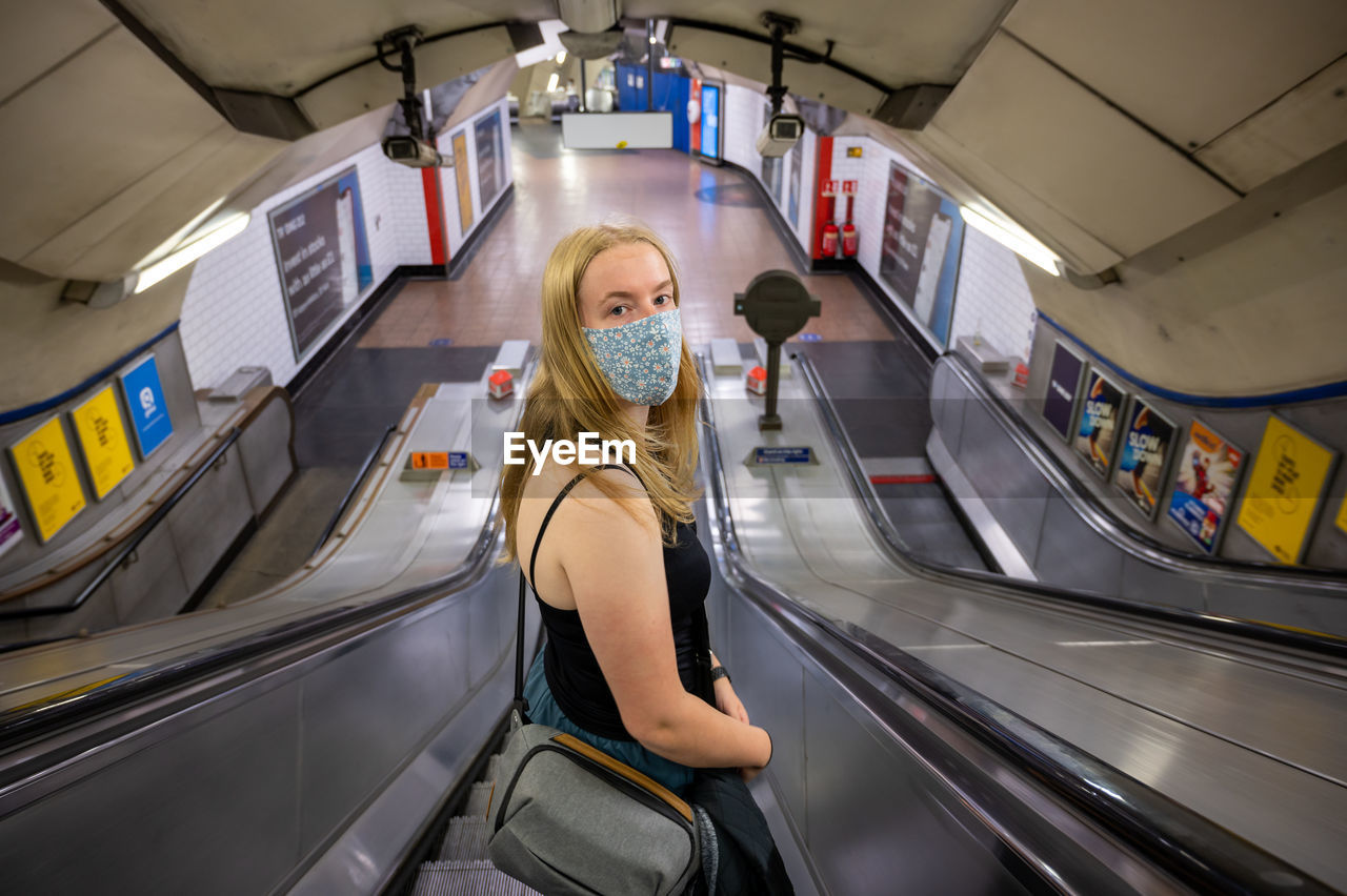 PORTRAIT OF YOUNG WOMAN STANDING ON ESCALATOR