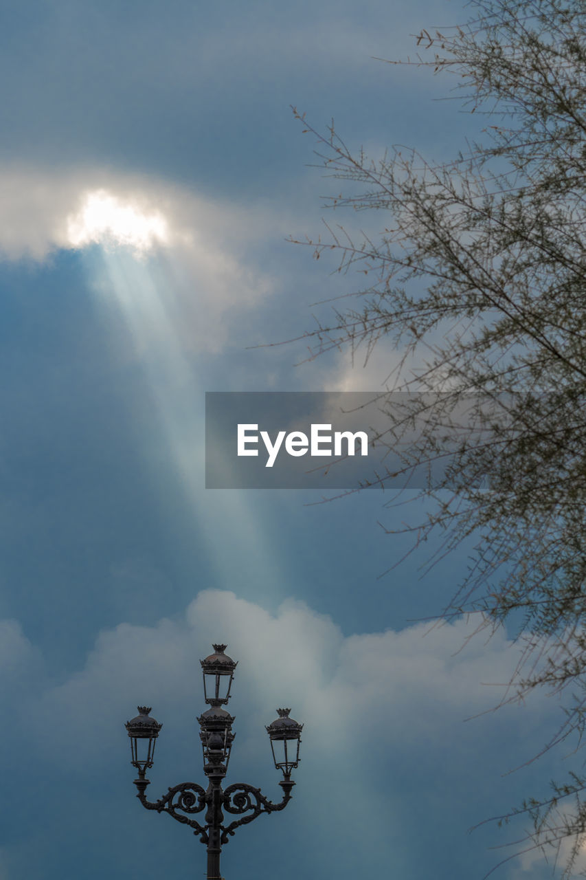 cloud - sky, sky, lighting equipment, low angle view, nature, no people, street light, street, sunlight, outdoors, day, tree, beauty in nature, architecture, electricity, sunbeam, built structure, metal, antique, electric lamp