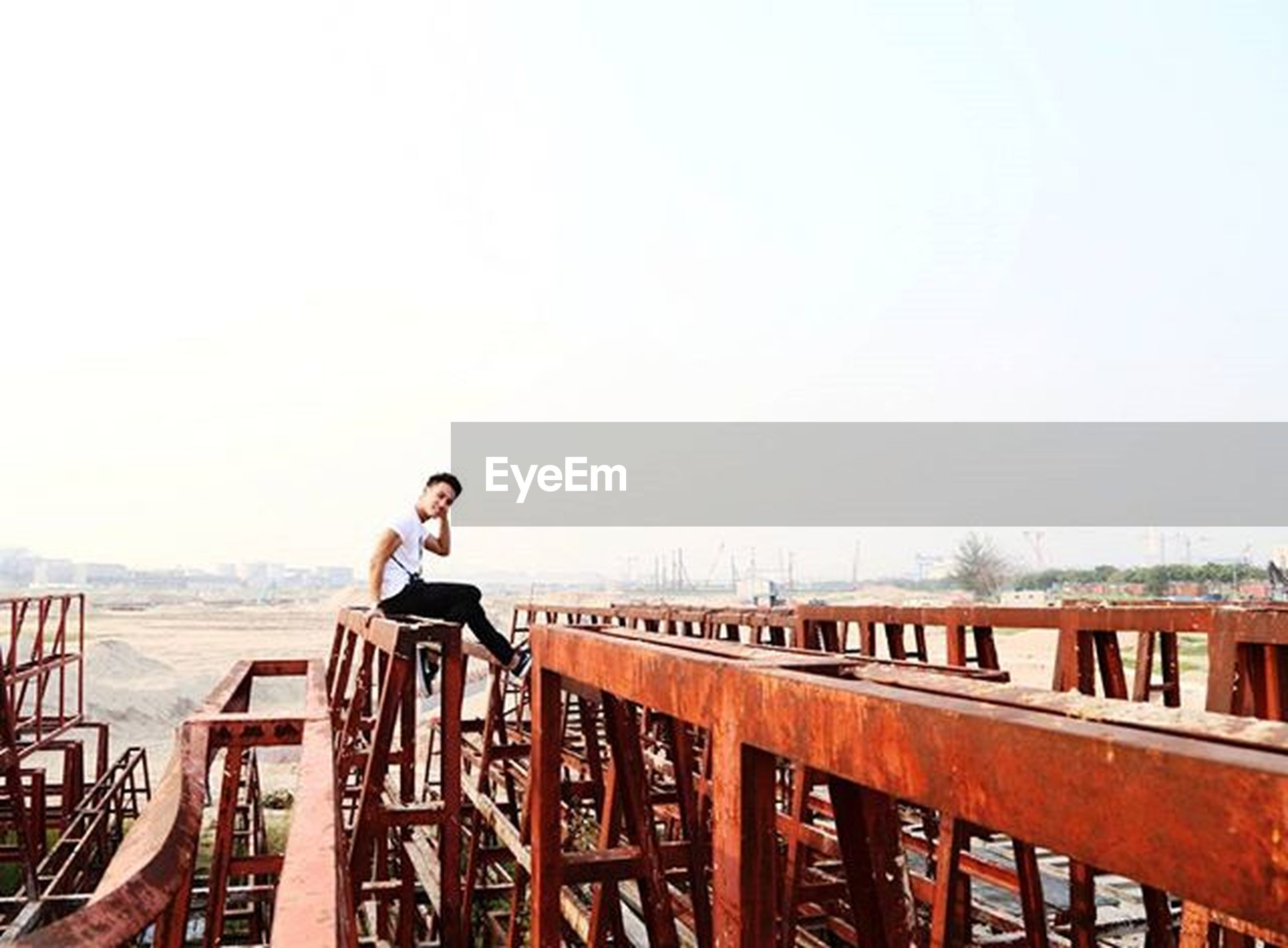 lifestyles, young adult, railing, clear sky, standing, casual clothing, leisure activity, copy space, person, waist up, young men, smiling, three quarter length, front view, portrait, sky, side view
