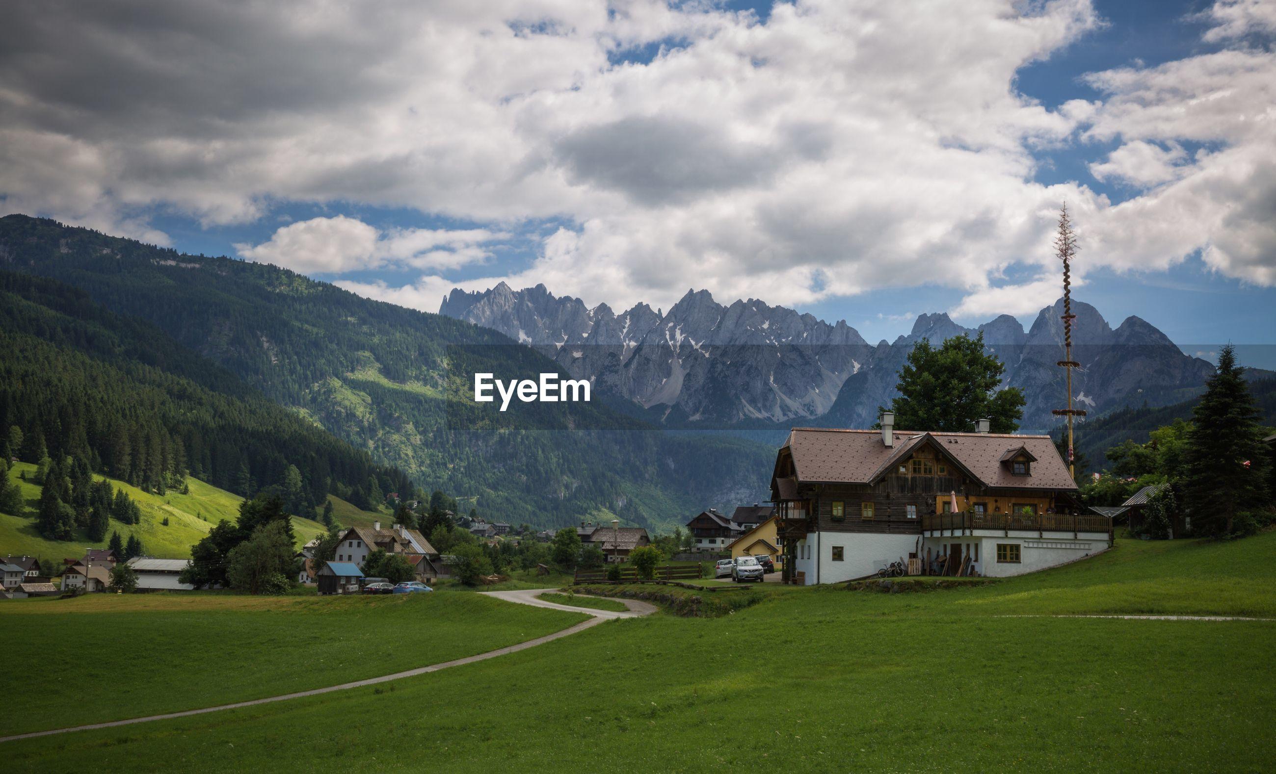 HOUSES ON LANDSCAPE AGAINST MOUNTAIN RANGE