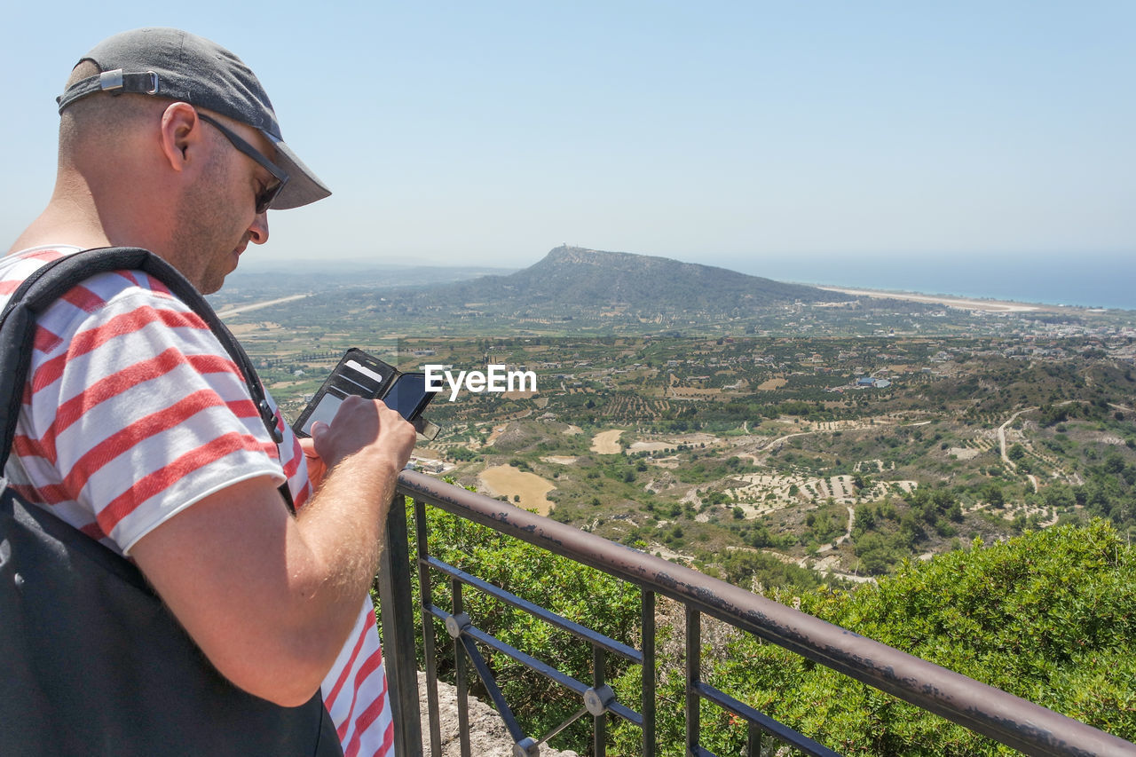 Man Using Mobile Phone While Standing By Railing On Mountain Against Clear Sky During Sunny Day