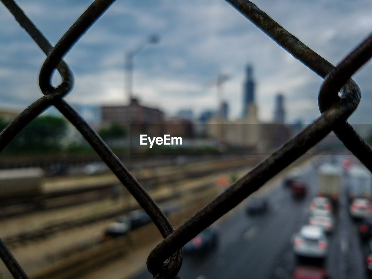 metal, chainlink fence, focus on foreground, protection, sky, mode of transport, no people, day, land vehicle, city, transportation, building exterior, outdoors, architecture, built structure, close-up, cloud - sky, cityscape