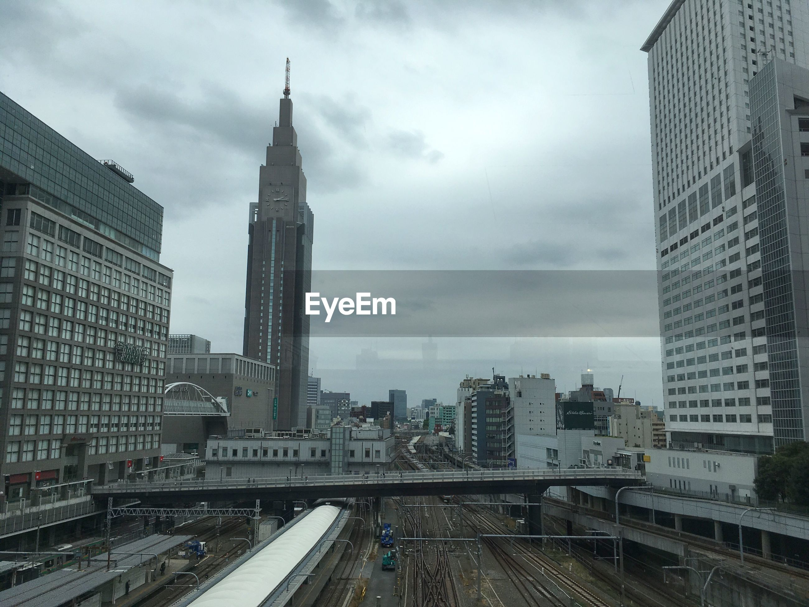 architecture, built structure, building exterior, city, building, sky, cloud - sky, tall - high, office building exterior, tower, skyscraper, cityscape, transportation, no people, rail transportation, mode of transportation, bridge, train, office, modern, bridge - man made structure, outdoors, financial district, spire