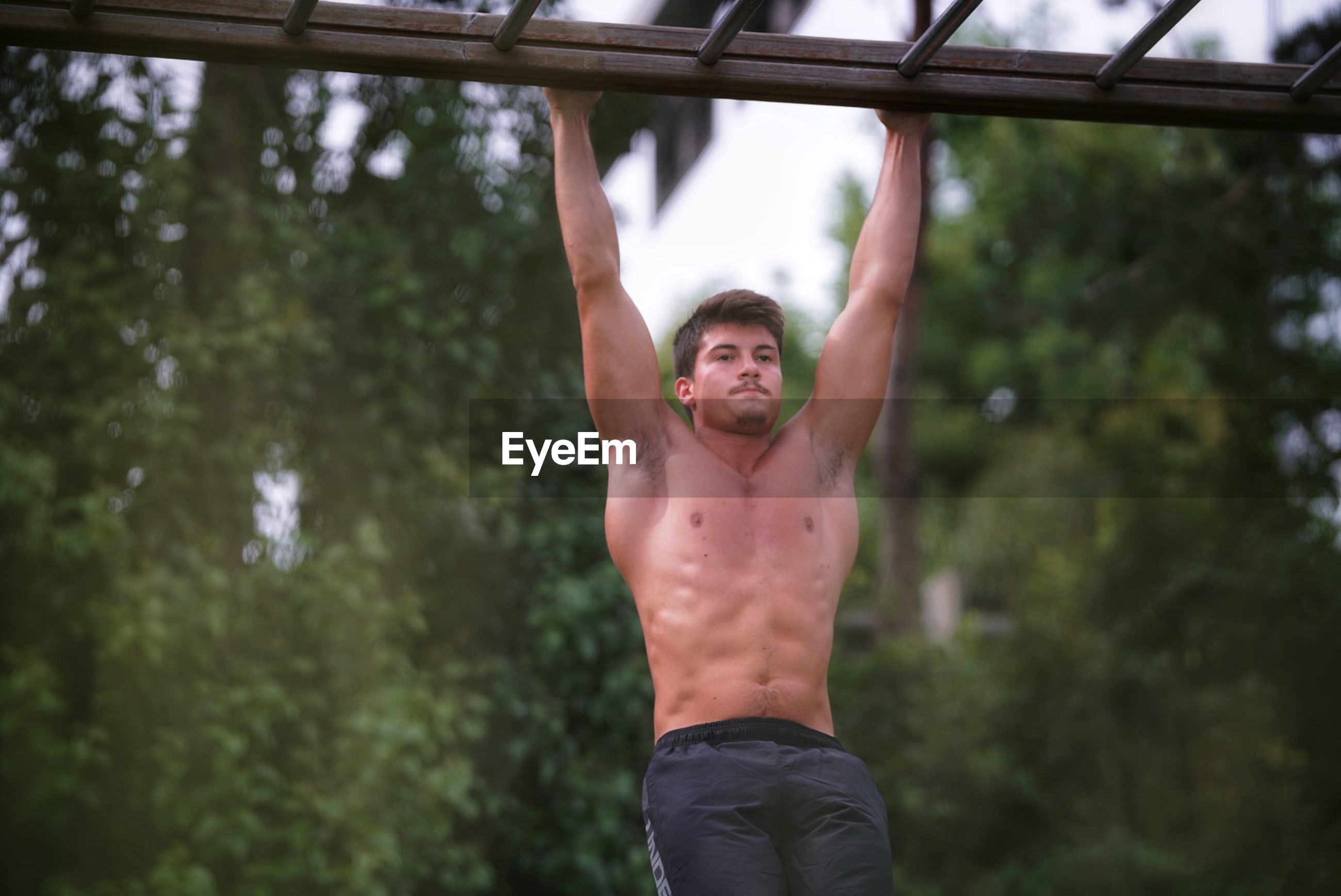 one person, shirtless, lifestyles, muscular build, young men, front view, real people, men, three quarter length, young adult, healthy lifestyle, adult, strength, day, standing, males, leisure activity, handsome, human arm, arms raised, masculinity, abdominal muscle