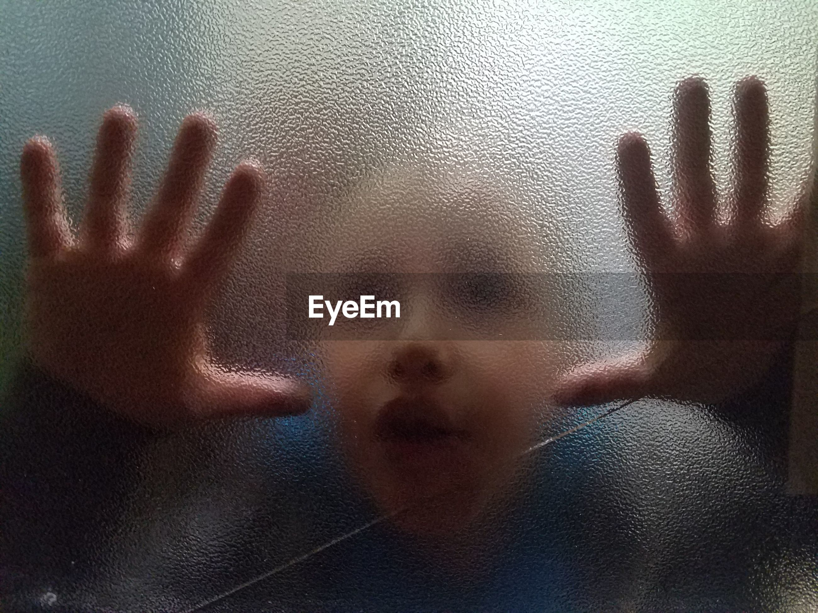 Close-up of boy seen through window