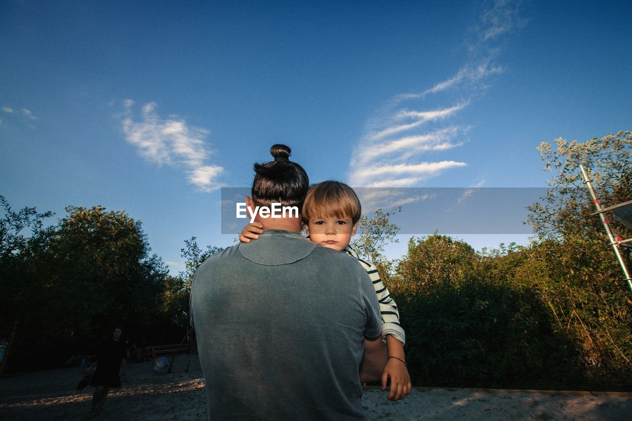 Rear View Of Father Carrying Son On Field Against Sky