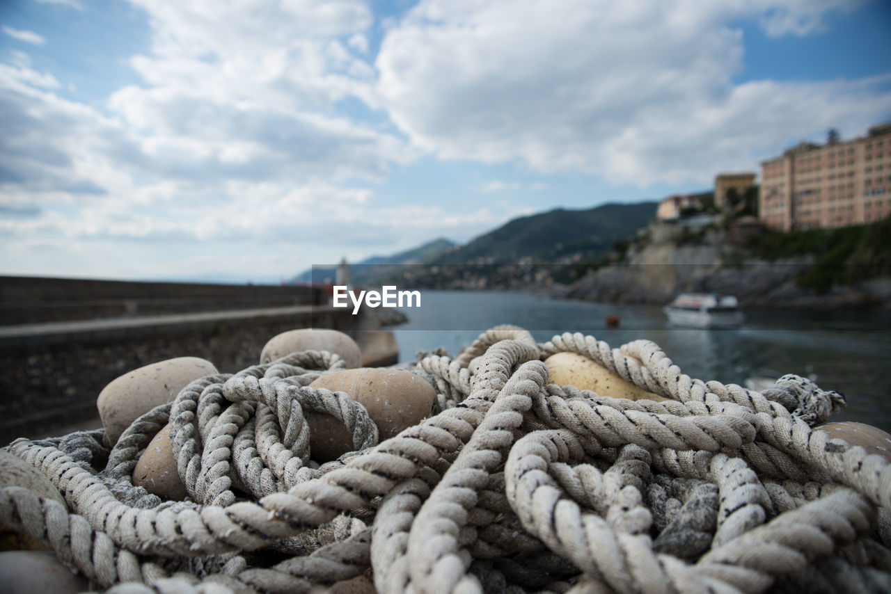Close-up of ropes and buoys in front of river