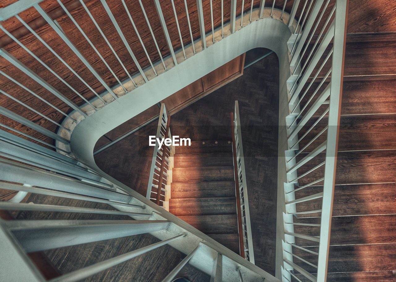architecture, built structure, indoors, steps and staircases, staircase, spiral, railing, spiral staircase, building, no people, pattern, high angle view, directly above, wood - material, design, day, metal, shape, diminishing perspective
