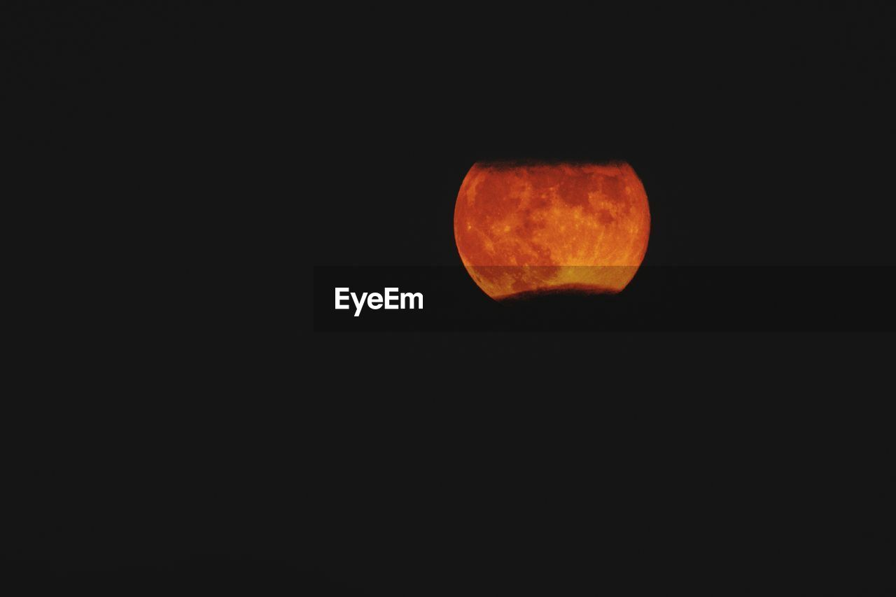 orange color, copy space, sky, space, night, astronomy, circle, no people, geometric shape, nature, clear sky, moon, beauty in nature, outdoors, shape, full moon, scenics - nature, tranquility, planetary moon, dark, black background, eclipse