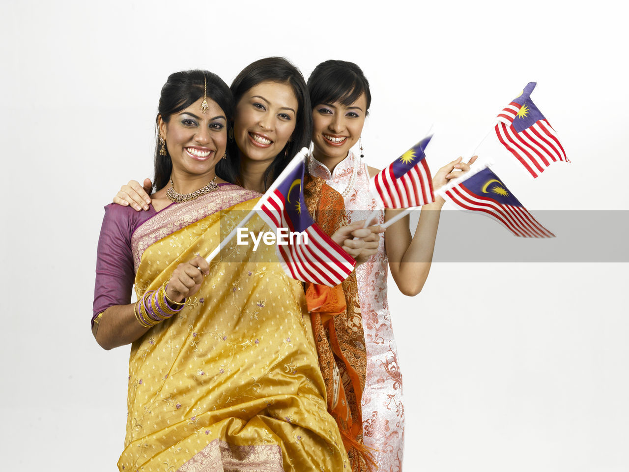 white background, studio shot, smiling, looking at camera, happiness, portrait, front view, standing, indoors, traditional clothing, emotion, holding, women, waist up, togetherness, young adult, cut out, patriotism, females, young women, positive emotion