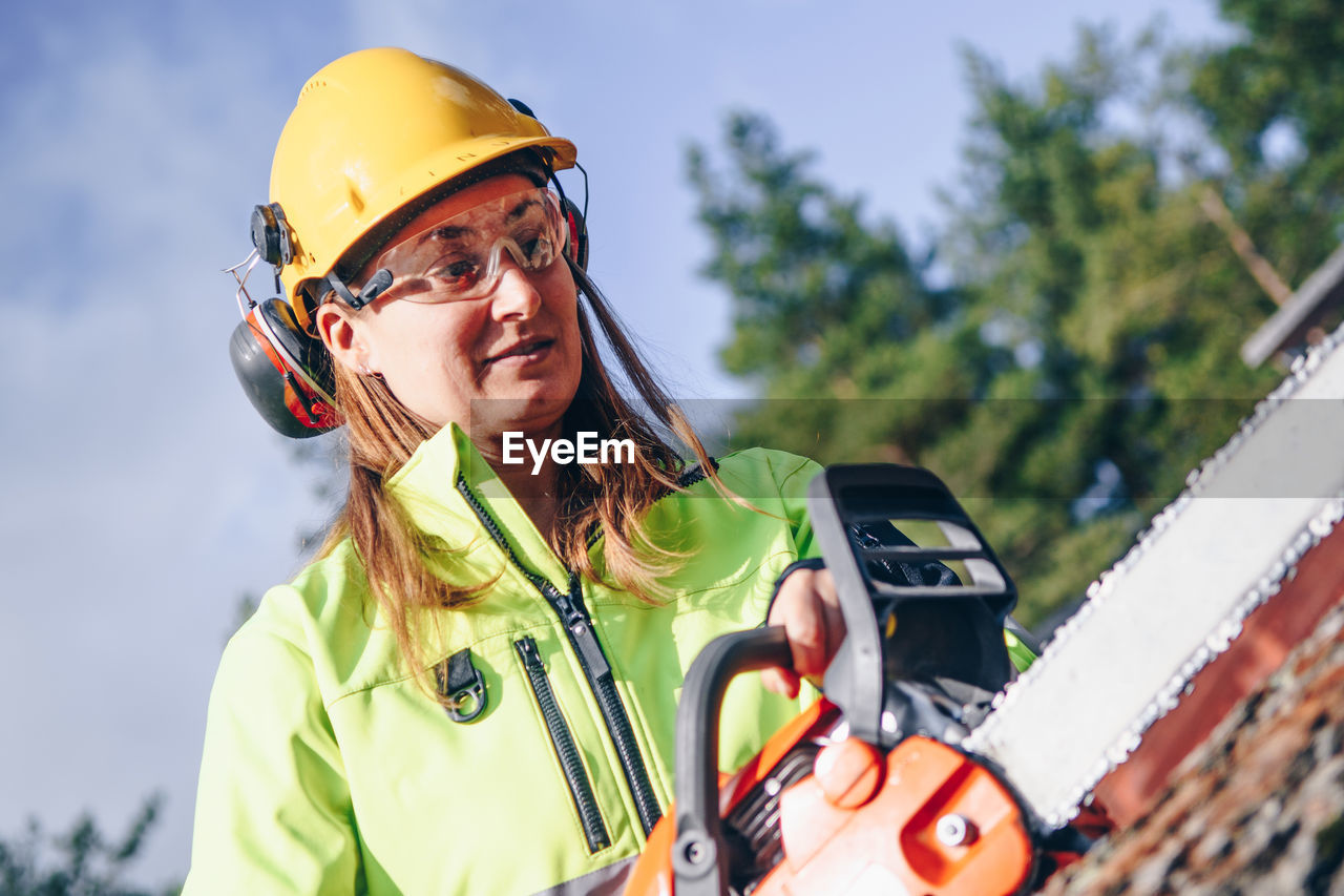 Female worker cutting tree trunk with electric saw